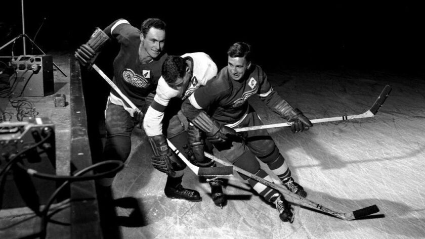 In this undated photo, Detroit Red Wings' Red Kelly, left, and Ted Lindsay, right, battle another te