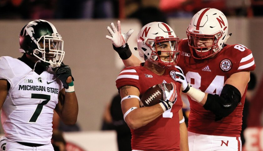 Nebraska wide receiver Jordan Westerkamp, center, is congratulated by teammate tight end Sam Cotton (84) after catching a touchdown pass as Michigan State defensive back Demetrious Cox (7) watches during the first half of an NCAA college football game in Lincoln, Neb., Saturday, Nov. 7, 2015. (AP P