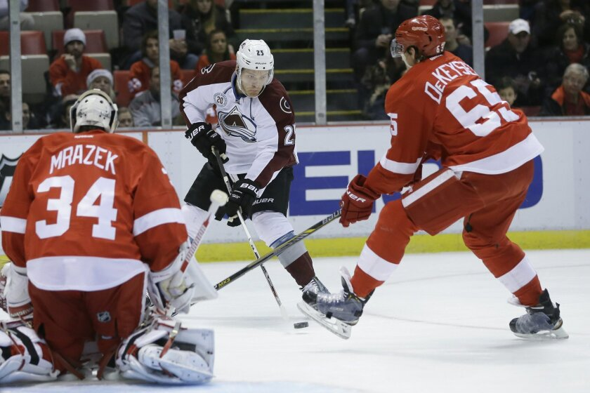 Colorado Avalanche center Mikhail Grigorenko (25), of Russia, passes the puck past Detroit Red Wings defenseman Danny DeKeyser (65) during the first period of an NHL hockey game Friday, Feb. 12, 2016, in Detroit. (AP Photo/Carlos Osorio)