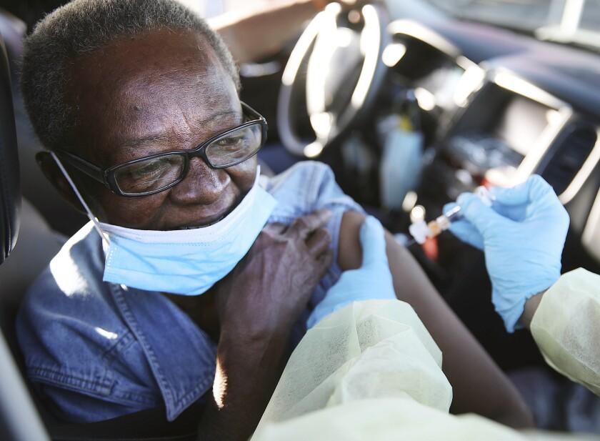 Patricia Martin receives a drive-through flu shot in her car in Tulsa, Okla.