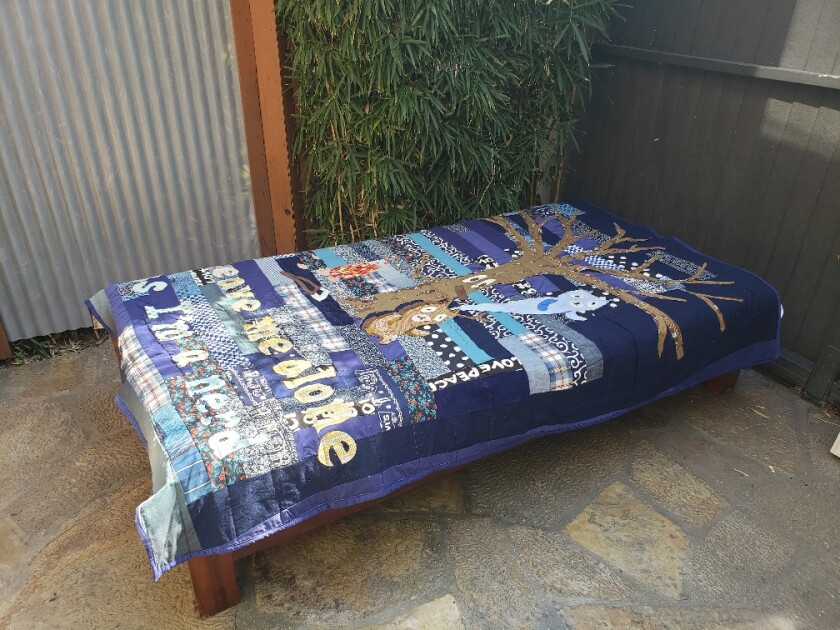 A poignant cross-cultural quilt by Atsushi Kaga is spread out on a cabana daybed.