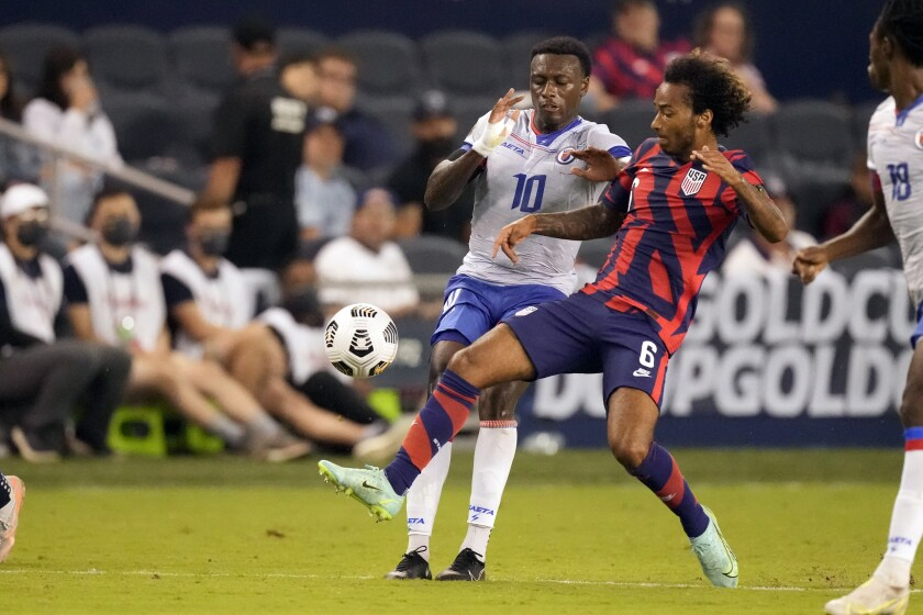 United States midfielder Gianluca Busio (6) kicks past Haiti midfielder Derrick Ettiene Jr. (10) during the second half of a CONCACAF Gold Cup soccer match Sunday, July 11, 2021, in Kansas City, Kan. The United States won 1-0. (AP Photo/Charlie Riedel)