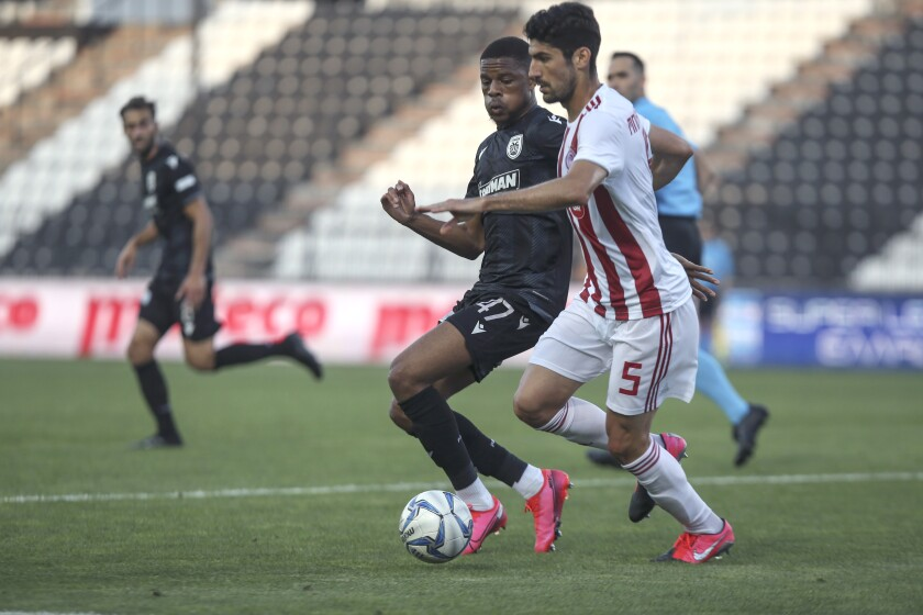 PAOK's Chuba Akpom challenges Olympiakos' Andreas Bouchalakis, foreground right, during their Super League soccer match, in Thessaloniki, northern Greece, Sunday, June 7, 2020. The Greek Super League returned to action this weekend, following almost three months of inactivity due to measures against the coronavirus pandemic. (AP Photo/Giannis Papanikos)