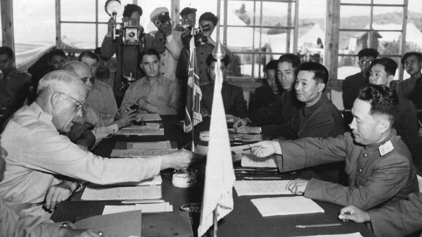 Maj. Gen. Blackshear M. Bryan, left, exchanges credentials with Lt. Gen. Lee Sang Cho at the opening session of the Military Armistice Commission at the Panmunjom Conference House on July 28, 1953.