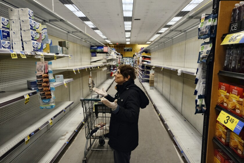 A gloved grocery shopper expresses dismay over the empty shelves at a Ralphs supermarket in Panorama City on Friday.