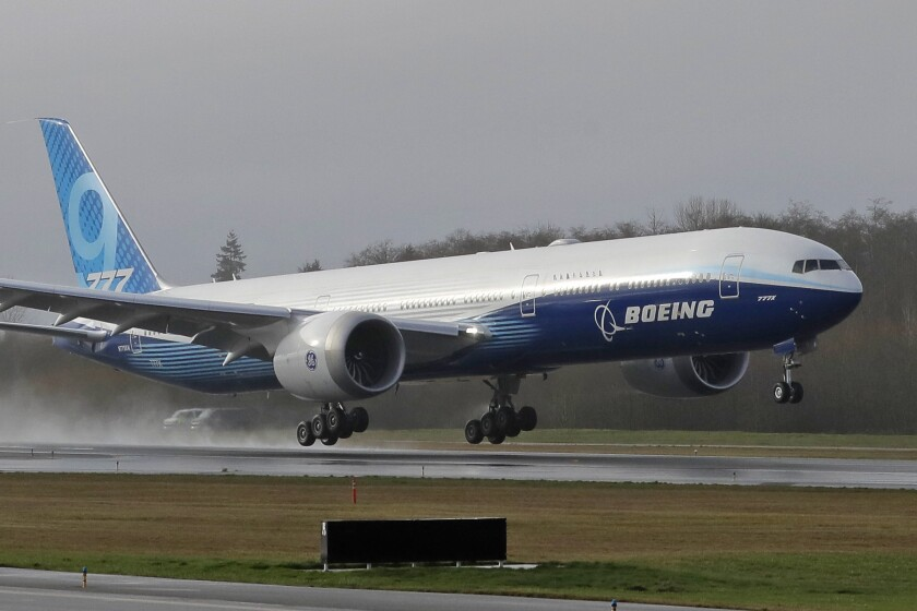 FILE - In this Jan. 25, 2020 file photo, a Boeing 777X airplane takes off on its first flight, at Paine Field in Everett, Wash. Boeing is painting a sobering picture for its business in 2020. The Chicago-based company said Wednesday, March 11 it has imposed a hiring freeze in response to the virus outbreak that is undercutting air travel. It said received 18 orders last month for new large planes but continues to lose orders for the grounded 737 Max. (AP Photo/Ted S. Warren, File)