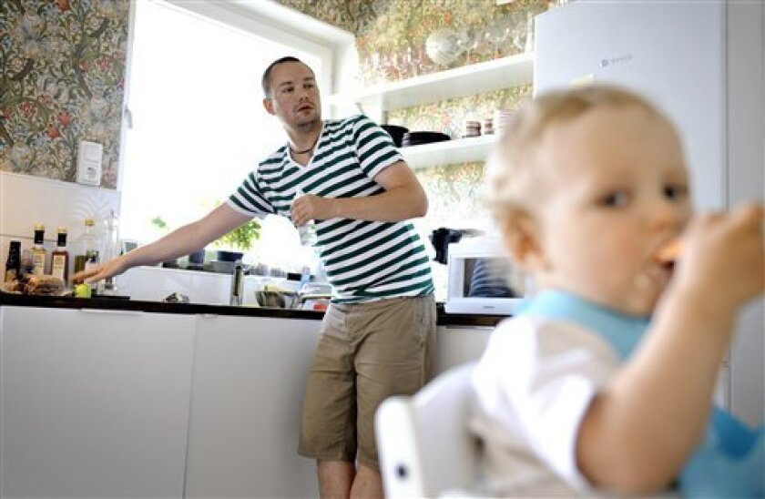 Henrik Holgersson cares for his son, Arvid, in the kitchen of their home in Stockholm. Holgersson has split Sweden's generous parental leave with his girlfriend Jenny Karlsson and is spending eight months at home with their child. Holgersson, who normally works as a rigger at an event company, says
