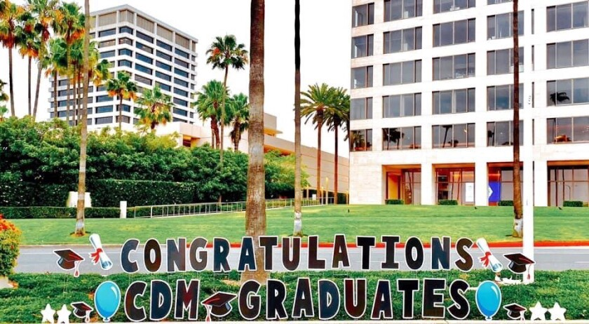 Signage congratulates graduates from Corona del Mar High School along the drive-by route on Saturday.