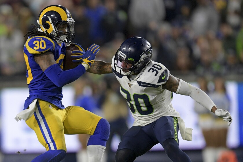 Los Angeles Rams running back Todd Gurley, left, runs past Seattle Seahawks strong safety Bradley McDougald during the second half of an NFL football game Sunday, Dec. 8, 2019, in Los Angeles.(AP Photo/Kyusung Gong)