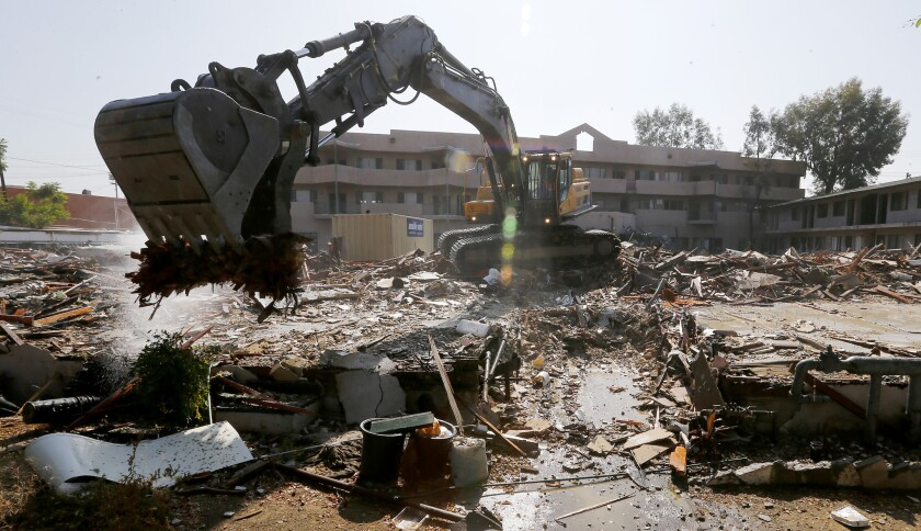 A heavy equipment operator demolishes the former Fiesta Motel in North Hollywood on Thursday. The motel served for 30 years as housing for some of the San Fernando Valley's homeless.