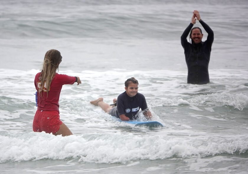 Sophia Saunders, 10, rides a wave as para surfer Liv Stone and Switchfoot drummer Chad Butler cheer her on.