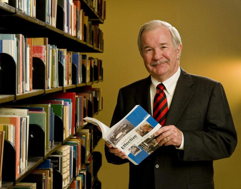 """Glen Broom holding """"Effective Public Relations,"""" a widely used textbook he co-authored."""