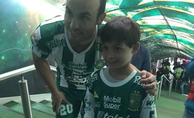 Donovan se toma una foto con un niño, minutos antes de la presentación con su nuevo equipo, el León, en la cancha del Camp Nou.