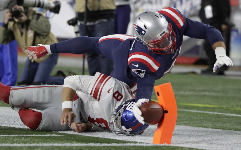 New England Patriots linebacker Kyle Van Noy dives over New York Giants quarterback Daniel Jones to score a touchdown after returning a fumble he recovered in the second half of an NFL football game, Thursday, Oct. 10, 2019, in Foxborough, Mass. (AP Photo/Elise Amendola)