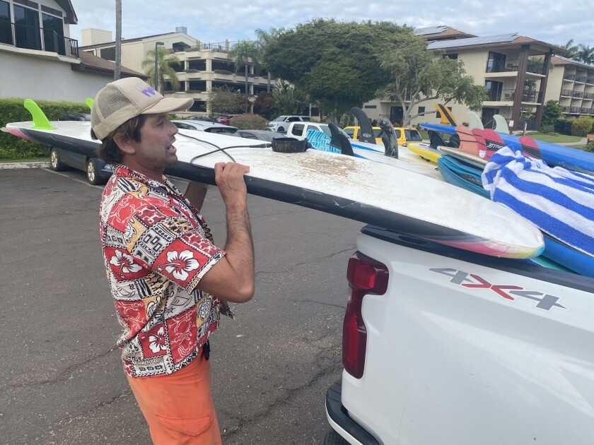 Kelley Hunt loads a surfboard into the back of a pickup.