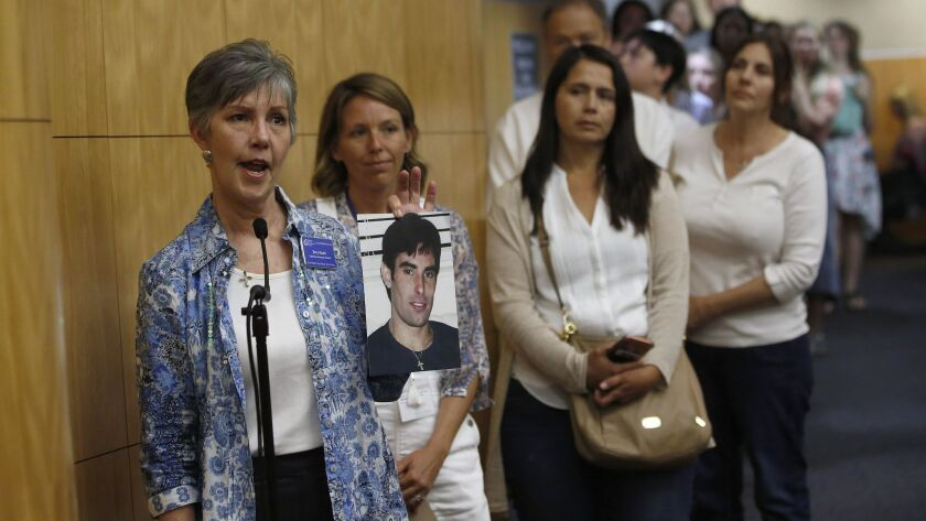Terry Roark displays a photo of her son, Thomas, who she said was harmed by vaccines given to him wh