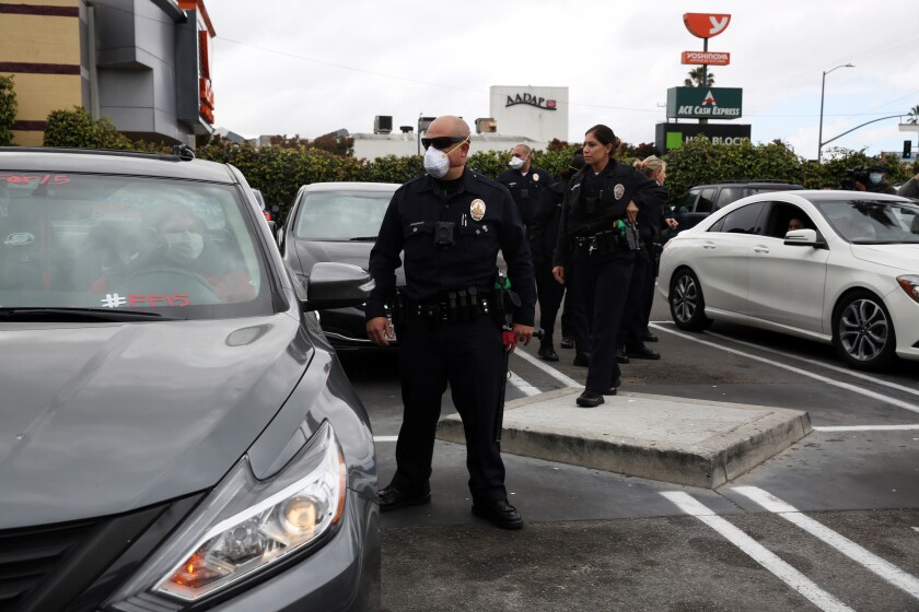 Los Angeles police officers wear masks while responding to a call in Crenshaw on Sunday.