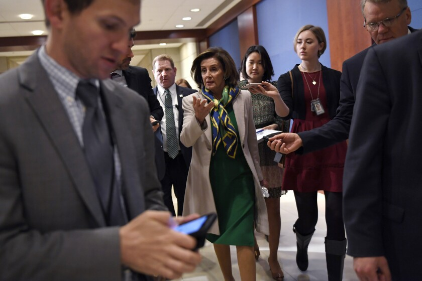 House Speaker Nancy Pelosi of Calif., is followed by reporters as she walks on Capitol Hill in Washington, Thursday, March 12, 2020. (AP Photo/Susan Walsh)