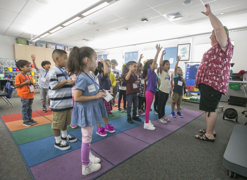 "Kindergarten teacher Jennifer Smart led her class in singing ""This Land is Your Land"" on Monday, the first day of class at Zamorano Elementary School in the Bay Terrace community of San Diego."
