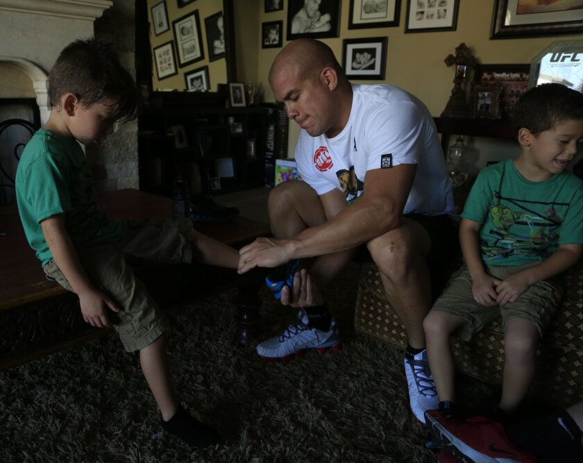 October 11th, 2014 Huntington Beach, CA- Mixed martial arts fighter Tito Ortiz put shoes on his son Jesse before they leave for dinner. Photo by David Brooks/ U-T San Diego MANDATORY PHOTO CREDIT DAVID BROOKS / U-T SAN DIEGO; ZUMA Press.