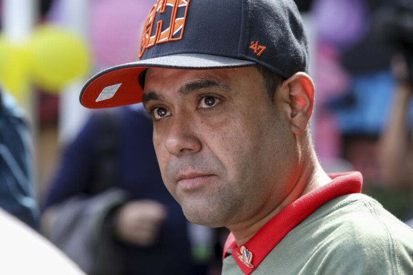 Miguel Perez Jr. listens to a supporter speaking at a news conference in Chicago on Tuesday, Sept. 24, 2019. Perez, an Army veteran who was deported to Mexico in 2018 arrived back in Chicago Tuesday for a final chance at becoming a U.S. citizen and living in the city he has called home since boyhood. (AP Photo/Teresa Crawford)