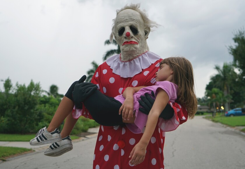 """""""Wrinkles the Clown"""" holds a little girl in his arms in a scene from the documentary."""