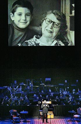 """Michael Tilson Thomas stands before a contingent of the Los Angeles Philharmonic beneath a projection of an early photo of himself with his celebrated grandmother, Bessie. The San Francisco Symphony's music director is paying tribute to his grandparents at Walt Disney Concert Hall with """"The Thomashefskys: Music and Memories of a Life in the Yiddish Theater."""""""