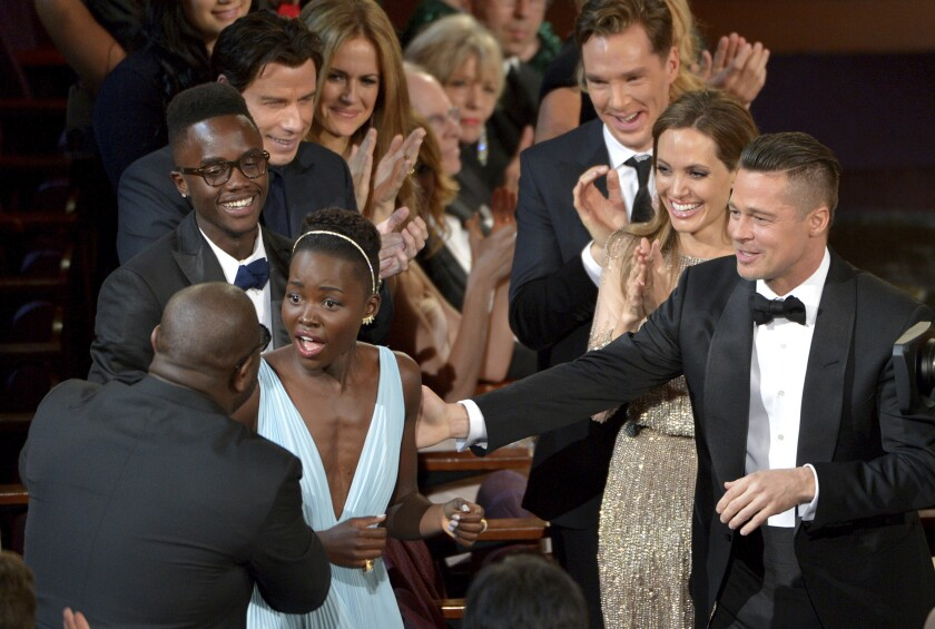 "FILE - In this March 2, 2014 file photo, director Steve McQueen, left, congratulates Lupita Nyong'o on her win for best actress in a supporting role for ""12 Years a Slave"" as, from background left, her brother Peter, John Travolta, Kelly Preston, Benedict Cumberbatch, Angelina Jolie, and Brad Pitt look on during the Oscars in Los Angeles. (Photo by John Shearer/Invision/AP, FIle)"