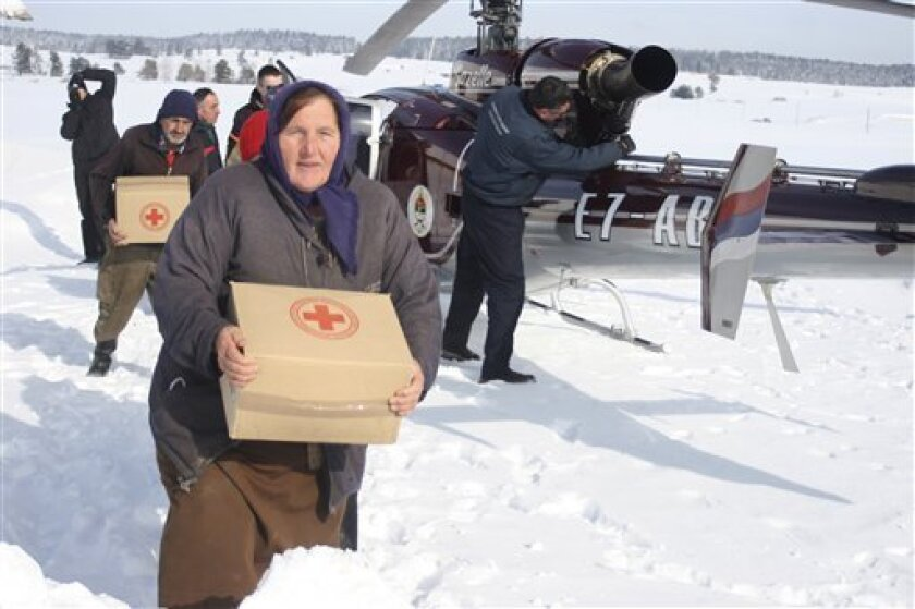 Bosnian people caring food supplies in a remote village, cut of by road due high snow fall, near Bosnian town of Sokolac, 70 kms east of Sarajevo, Bosnia, on Wednesday, Feb. 1, 2012 .Rescue helicopters are airlifting supplies and evacuating dozens of people from snow-covered villages in Bosnia, as the death toll from Eastern Europe's severe cold spell has risen to 79. Central and eastern Europe are experiencing a severe and snowy cold snap with temperatures in Bosnia plummeting to lows of minus 10 Celsius (14 degrees Fahrenheit).(AP Photo/Radul Radovanovic)