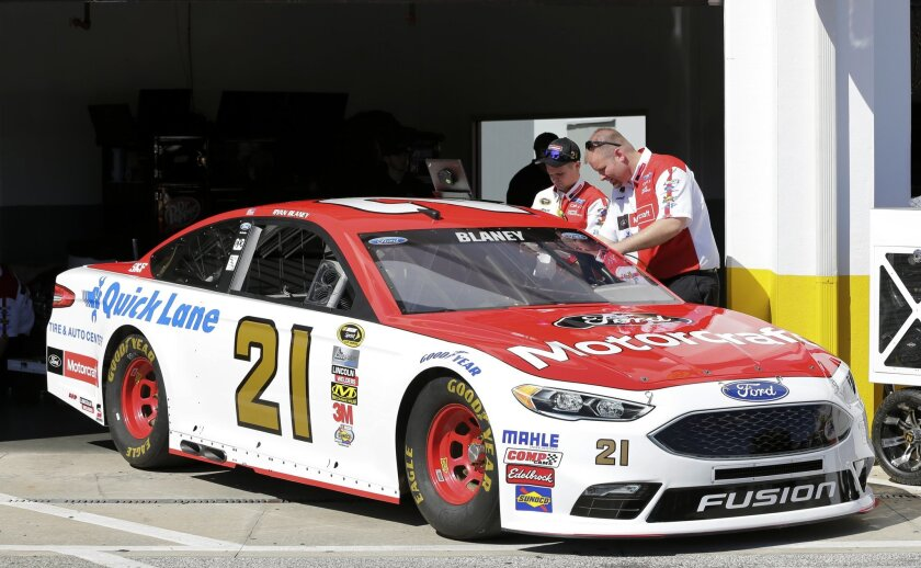 Crew members of the Wood Brothers team NASCAR auto racing car that Ryan Blaney will drive prepare the car for a practice session at Daytona International Speedway, Friday, Feb. 12, 2016, in Daytona Beach, Fla. (AP Photo/Terry Renna)