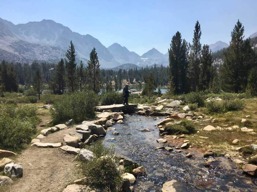 A hiker crosses a stream in the Little Lakes Valley of Inyo National Forest on Aug. 28, 2020.