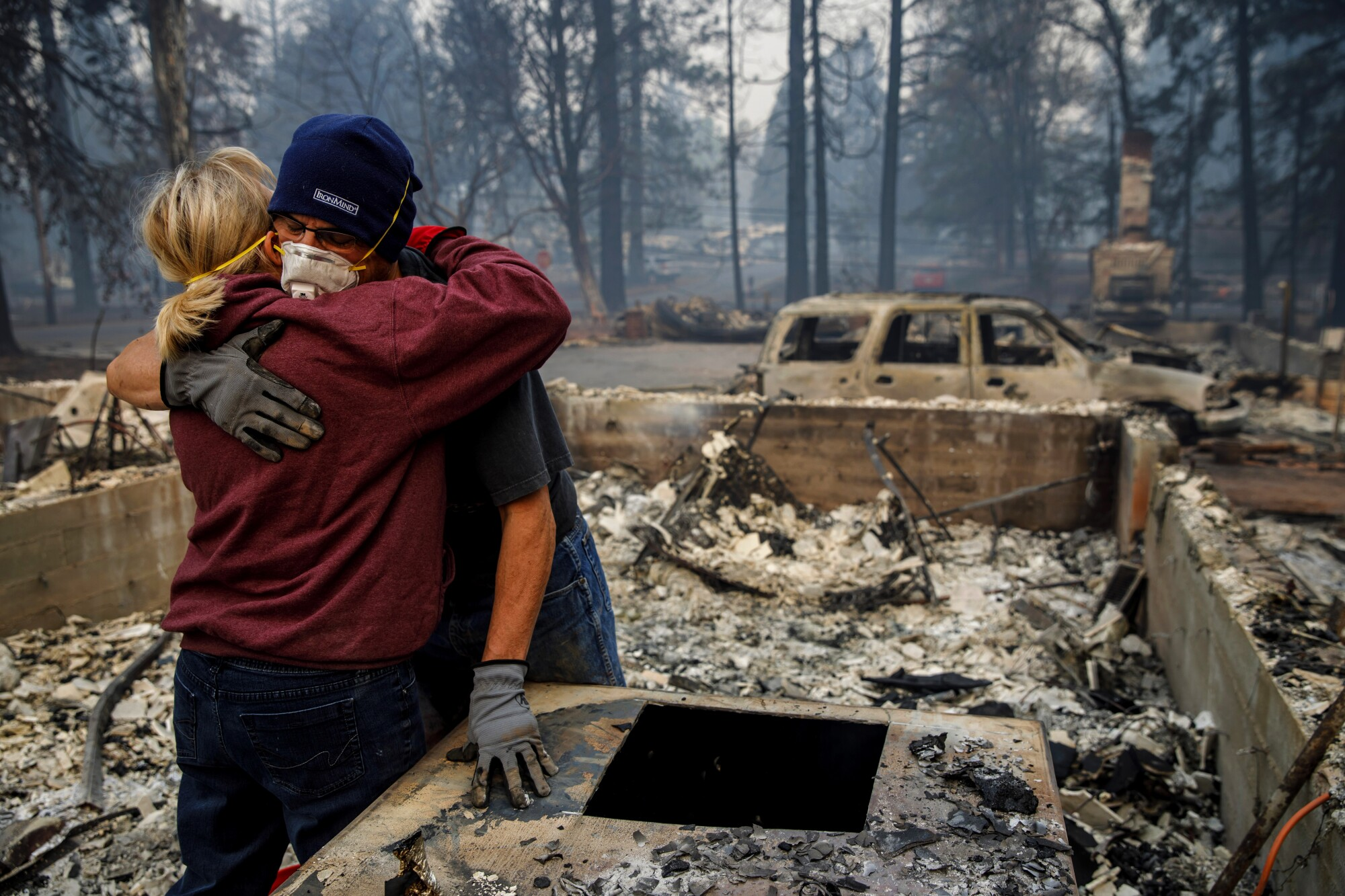 MICHAEL JOHN RAMIREZ hugs his wife, Charlie, as they search the ruins of their Paradise home after the Camp fire.