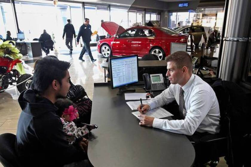 Sales representative Rafal Kubus, right, assists customers at a Ford dealership in Niles, Ill. Ford said it sold nearly 5,000 of its new C-Max hybrid in November, up about 50% from October.