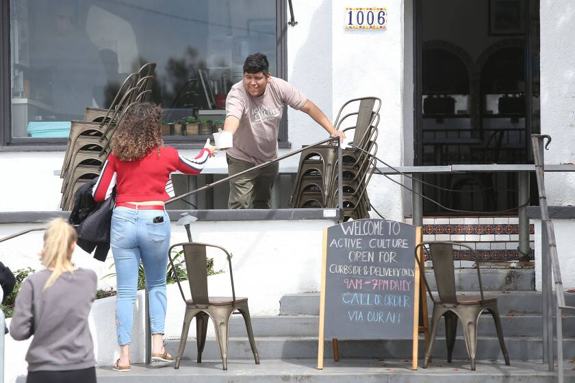 A patron arrives for curbside delivery at Active Culture in Laguna Beach as local businesses are being asked to avoid small gatherings and uphold social distances during the widening coronavirus pandemic.