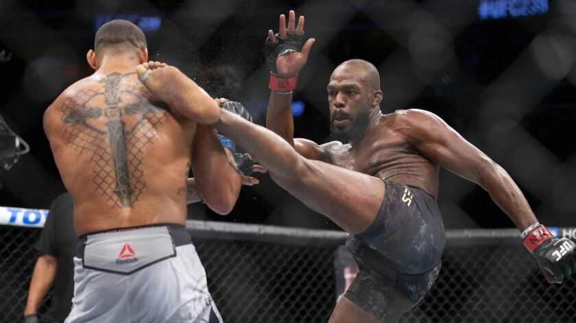 Jon Jones, right, lands a kick on Thiago Santos during their during their light heavyweight mixed ma