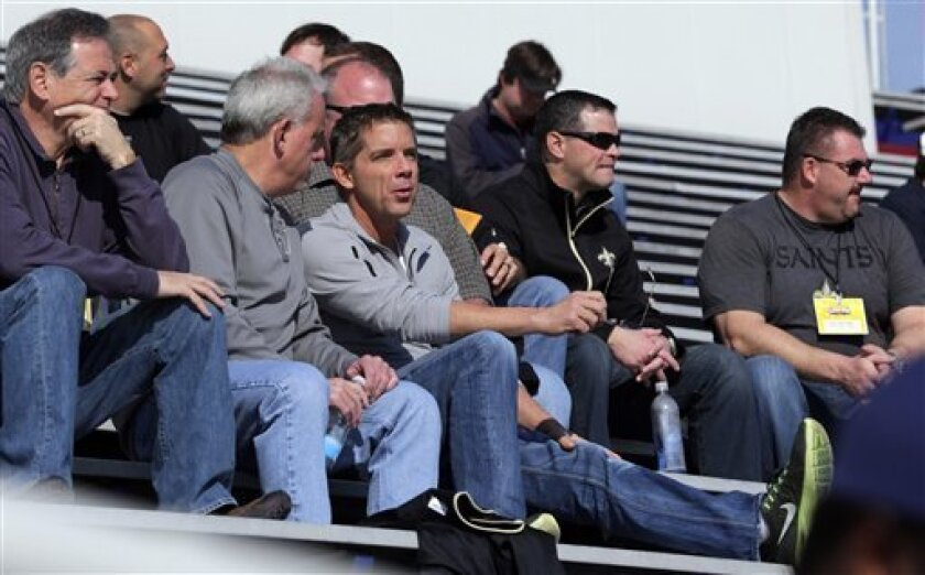 New Orleans Saints coach Sean Payton, center, talks with assistant head coach Joe Vitt, second from left, during Senior Bowl football practice at Ladd-Peebles Stadium in Mobile, Ala., Wednesday, Jan. 23, 2013. The NFL reinstated Payton on Tuesday following a season long suspension. Vitt served has