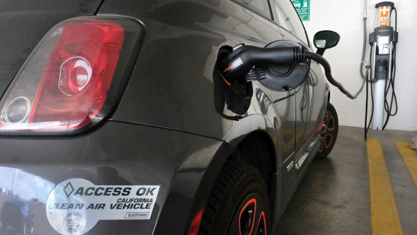 This April 25, 2016, photo shows an electric Fiat plugged into a charging station in a parking lot i
