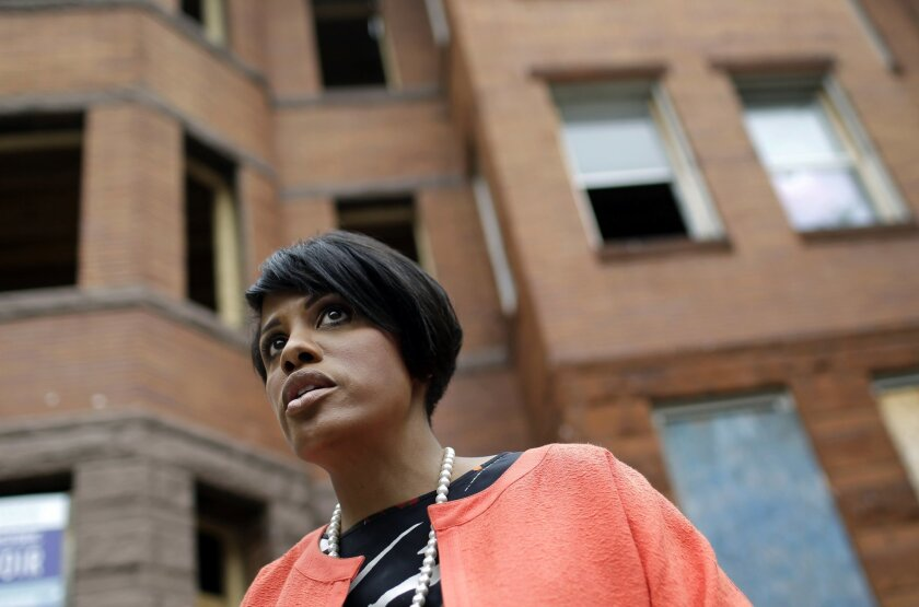 In this photo taken Tuesday, July 21, 2015, Baltimore Mayor Stephanie Rawlings-Blake stands outside vacant homes before a ceremony to kick off their restoration in Baltimore. For many in Baltimore, the memory of April's riots - and the mayor's handling of the unrest - is still fresh. After firing embattled police commissioner Anthony Batts, who bore the brunt of public outrage, Rawlings-Blake remains the primary figure head of a city that is still reeling from the damage it suffered. (AP Photo/Patrick Semansky)