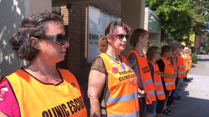 In this Monday, July 17, 2017, photo, Meg Stern, left, and other escort volunteers are lined up outs