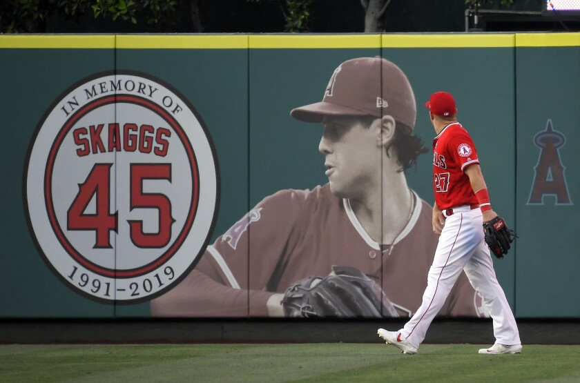 Mike Trout walks by a picture of late Angels pitcher Tyler Skaggs in center field at Angel Stadium