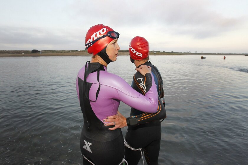Amy Dixon, a blind triathlete, left, and Susanne Davis prepare for the Tritonman triathlon in Mission Bay. Dixon is training for the Paralympics in Rio de Janeiro and Davis, a world Ironman Champion, is her guide and training partner. This was their first competition training together.