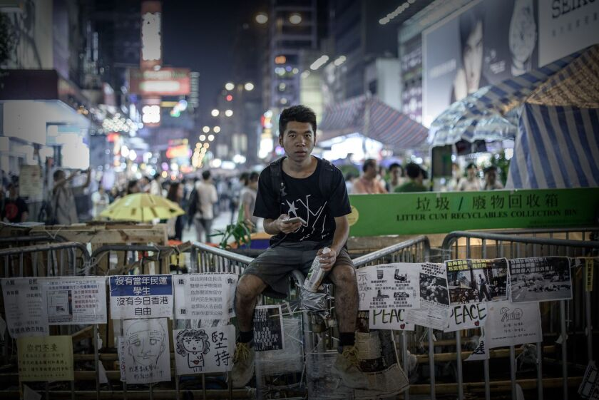 A pro-democracy protester sits on a barricade at a protest site in the Mong Kok district of Hong Kong on Oct. 26.
