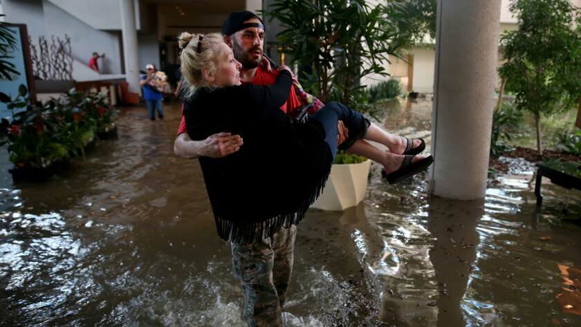 Rescue worker Adam Caballero carries CaroLine Kirkpatrick through an Omni Hotel as mandatory evacuation orders went into effect after the Addicks Reservoir overflowed.