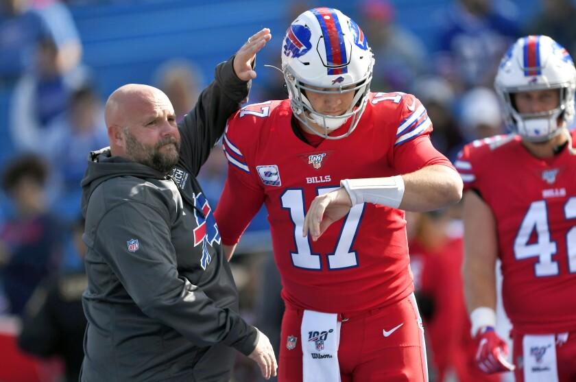 Buffalo Bills offensive coordinator Brian Daboll pats quarterback Josh Allen on the helmet before a game.