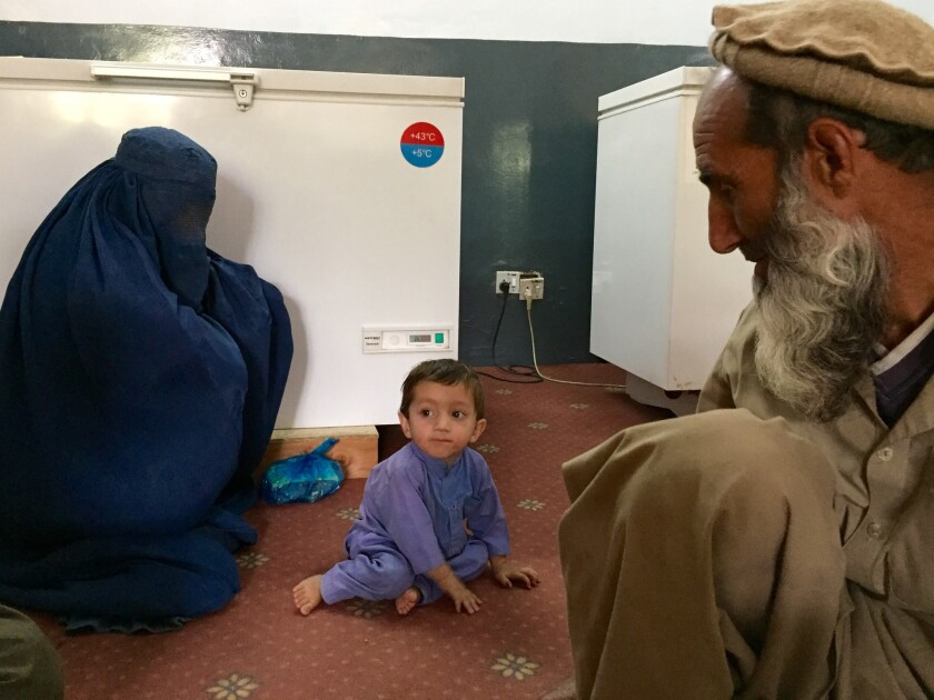 Khaksar is watched by his grandfather, Duran, at right, and his mother before an appointment with doctors in Asadabad, Afghanistan.