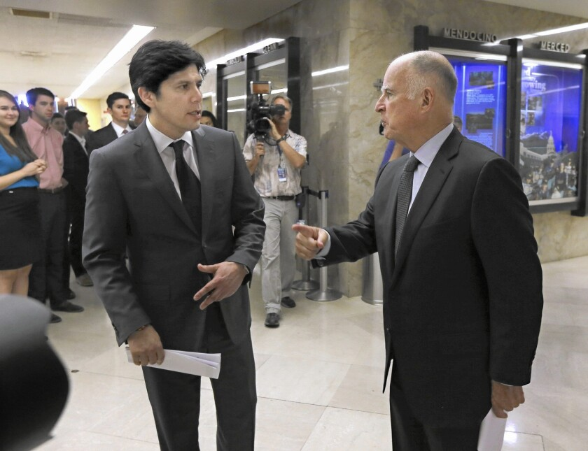 State Senate leader Kevin de León (D-Los Angeles), left, and Gov. Jerry Brown are working together to secure support from utilities for climate-change legislation that would increase the state's use of renewable energy.