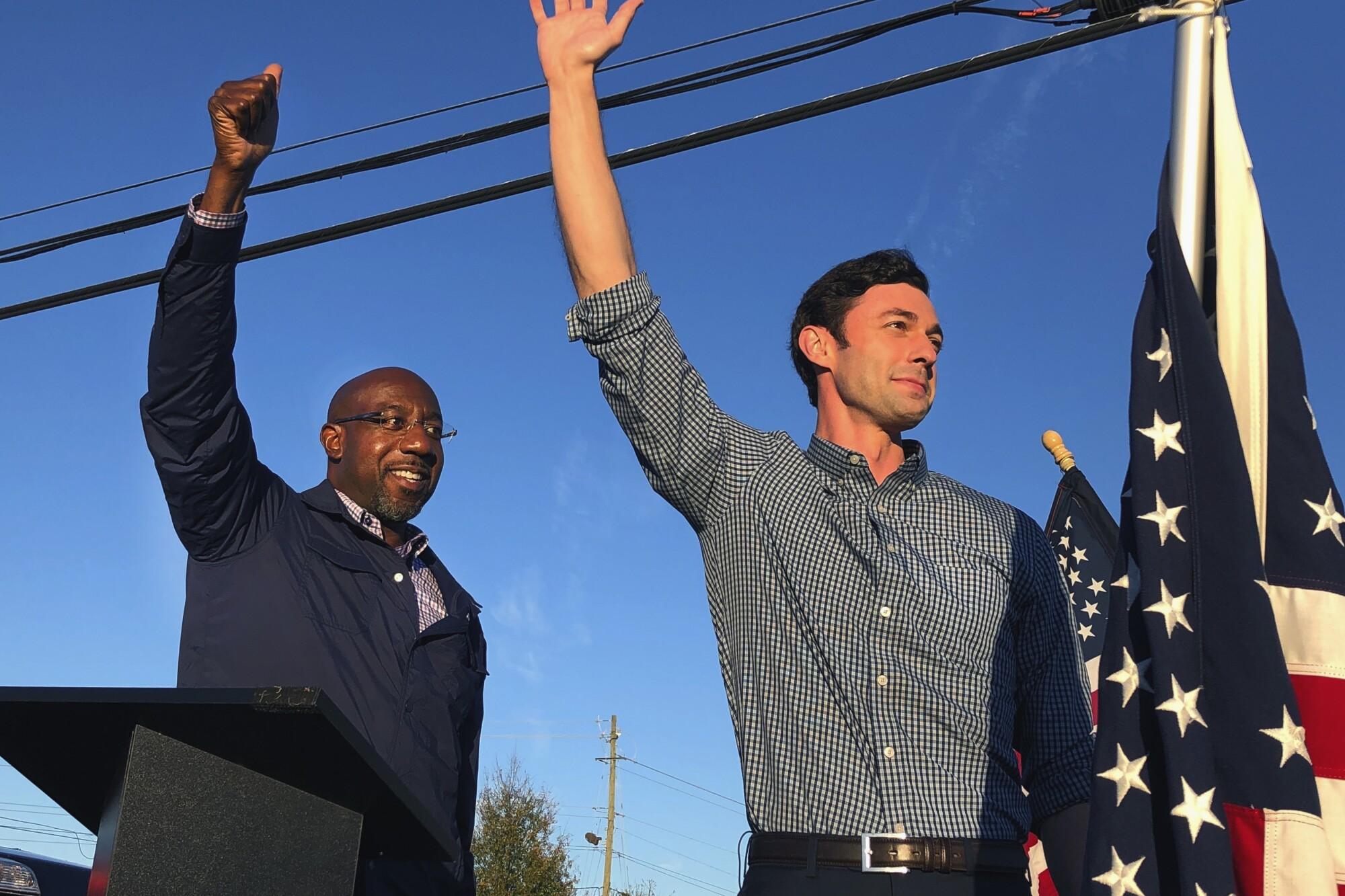 Democratic U.S. Senate candidates Raphael Warnock and Jon Ossoff wave to the crowd at a rally Nov. 15 in Marietta, Ga.