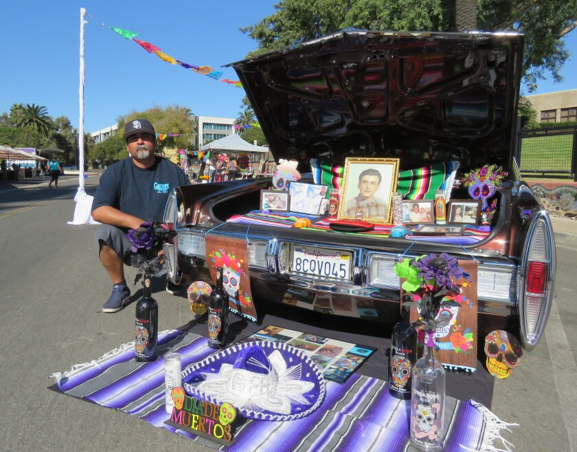 National City resident Jesus Ocampo kneels near the altar he set up in and in front of the trunk of his 1967 Cadillac.