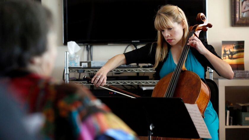 Cellist Erin Breene performs in the La Jolla living room of Marty and Sherry Bloom.
