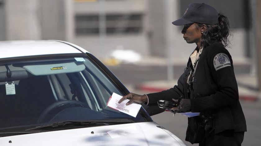 A parking enforcement officer tickets a car parked in Hollywood on a street-sweeping day.